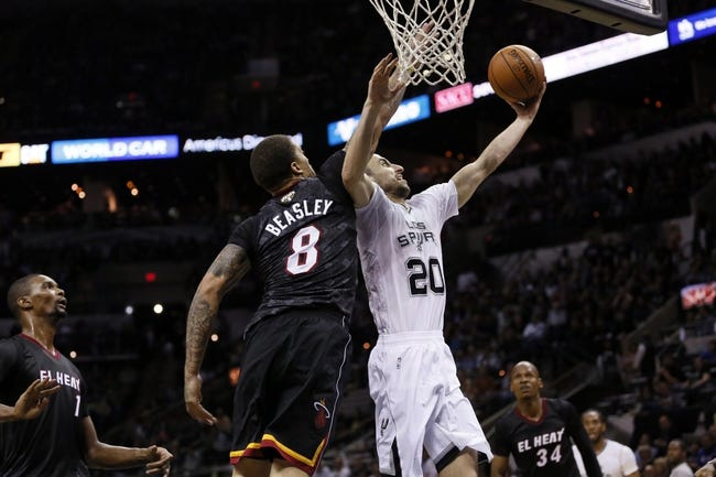 Mar 6, 2014; San Antonio, TX, USA; San Antonio Spurs guard Manu Ginobili (20) shoots the ball past Miami Heat forward Michael Beasley (8) during the second half at AT&T Center. The Spurs won 111-87. Mandatory Credit: Soobum Im-USA TODAY Sports