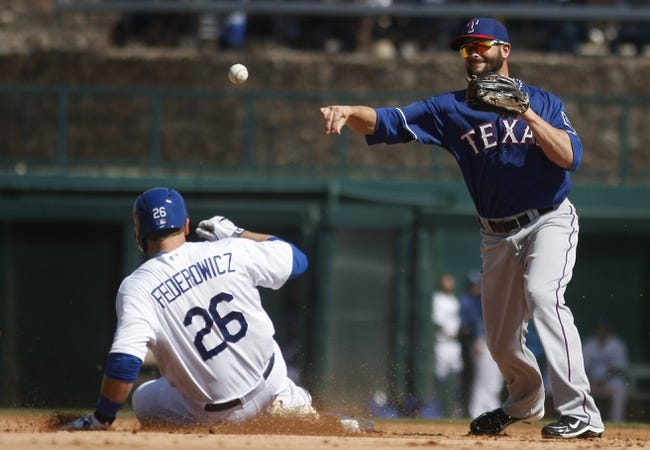 Mar 7, 2014; Phoenix, AZ, USA; Texas Rangers second baseman Andy Parrino (71)  turns the double play in the second inning while avoiding Los Angeles Dodgers catcher Tim Federowicz (26) at Camelback Ranch. Mandatory Credit: Rick Scuteri-USA TODAY Sports