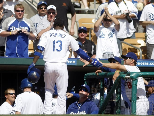 Mar 7, 2014; Phoenix, AZ, USA; Los Angeles Dodgers shortstop Hanley Ramirez (13) gets five from manager Don Mattingly (8) against the Texas Rangers after hitting a homerun in the first inning at Camelback Ranch. Mandatory Credit: Rick Scuteri-USA TODAY Sports