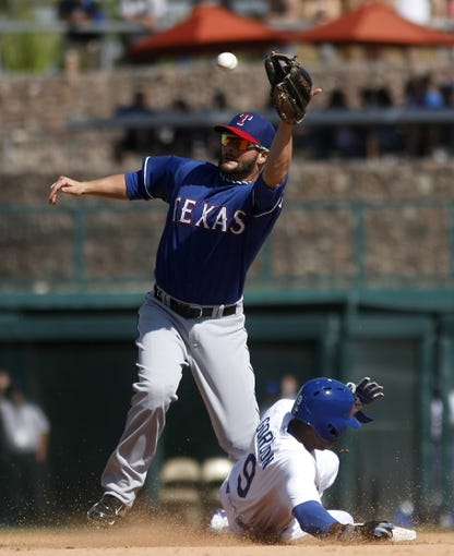 Mar 7, 2014; Phoenix, AZ, USA; Los Angeles Dodgers shortstop Dee Gordon (9) steals second base in the fifth inning in front of Texas Rangers second baseman Andy Parrino (71) at Camelback Ranch. Mandatory Credit: Rick Scuteri-USA TODAY Sports
