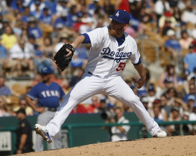 Mar 7, 2014; Phoenix, AZ, USA; Los Angeles Dodgers relief pitcher J.P. Howell (56) throws in the fifth inning against the Texas Rangers at Camelback Ranch. Mandatory Credit: Rick Scuteri-USA TODAY Sports