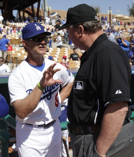 Mar 7, 2014; Phoenix, AZ, USA; Los Angeles Dodgers manager Don Mattingly (8) talks to a MLB umpire before a game against the Texas Rangers at Camelback Ranch. Mandatory Credit: Rick Scuteri-USA TODAY Sports