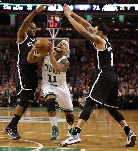 Mar 7, 2014; Boston, MA, USA; Boston Celtics point guard Jerryd Bayless (11) cuts between Brooklyn Nets shooting guard Marcus Thornton (10) and point guard Deron Williams (8) during the second half of Boston's 91-84 win at TD Garden. Mandatory Credit: Winslow Townson-USA TODAY Sports