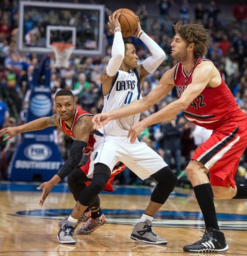 Mar 7, 2014; Dallas, TX, USA; Dallas Mavericks shooting guard Monta Ellis (11) steals the ball away from Portland Trail Blazers point guard Damian Lillard (0) and center Robin Lopez (42) to seal the win at the American Airlines Center. The Mavericks defeated the Trail Blazers 103-98. Mandatory Credit: Jerome Miron-USA TODAY Sports