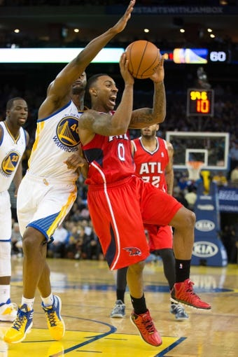 Mar 7, 2014; Oakland, CA, USA; Atlanta Hawks point guard Jeff Teague (0) passes out the ball against Golden State Warriors small forward Harrison Barnes (40) during the second quarter at Oracle Arena. Mandatory Credit: Kelley L Cox-USA TODAY Sports