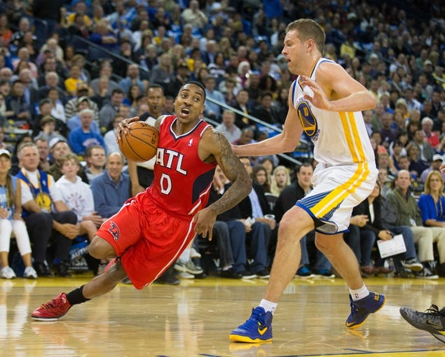 Mar 7, 2014; Oakland, CA, USA; Atlanta Hawks point guard Jeff Teague (0) slips on the play against Golden State Warriors power forward David Lee (10) during the second quarter at Oracle Arena. Mandatory Credit: Kelley L Cox-USA TODAY Sports