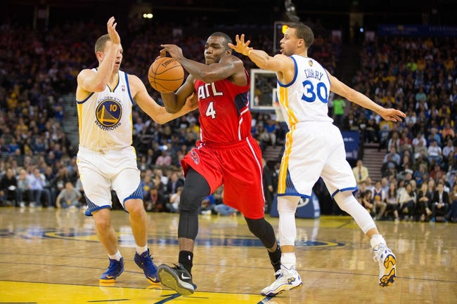 Mar 7, 2014; Oakland, CA, USA; Atlanta Hawks power forward Paul Millsap (4) drives in against Golden State Warriors power forward David Lee (10) and point guard Stephen Curry (30) during the second quarter at Oracle Arena. Mandatory Credit: Kelley L Cox-USA TODAY Sports