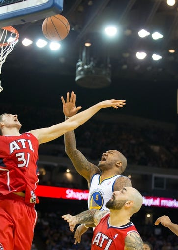 Mar 7, 2014; Oakland, CA, USA; Golden State Warriors power forward Marreese Speights (5) goes up for a layup against Atlanta Hawks center Mike Muscala (31) and center Pero Antic (6) during the fourth quarter at Oracle Arena. The Golden State Warriors defeated the Atlanta Hawks 111-97. Mandatory Credit: Kelley L Cox-USA TODAY Sports