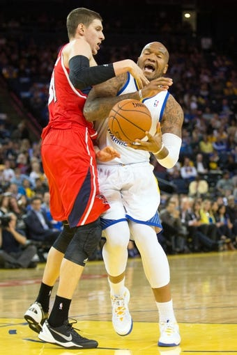Mar 7, 2014; Oakland, CA, USA; Atlanta Hawks center Mike Muscala (31) fouls Golden State Warriors power forward Marreese Speights (5) during the fourth quarter at Oracle Arena. The Golden State Warriors defeated the Atlanta Hawks 111-97. Mandatory Credit: Kelley L Cox-USA TODAY Sports