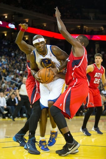 Mar 7, 2014; Oakland, CA, USA; Golden State Warriors center Jermaine O'Neal (7) controls the ball between Atlanta Hawks power forward Elton Brand (42) and power forward Paul Millsap (4) during the fourth quarter at Oracle Arena. The Golden State Warriors defeated the Atlanta Hawks 111-97. Mandatory Credit: Kelley L Cox-USA TODAY Sports