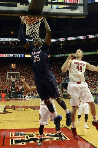 Mar 8, 2014; Louisville, KY, USA; Connecticut Huskies center Amida Brimah (35) dunks against Louisville Cardinals forward Stephan Van Treese (44) during the first half at KFC Yum! Center. Louisville defeated Connecticut 81-48.  Mandatory Credit: Jamie Rhodes-USA TODAY Sports
