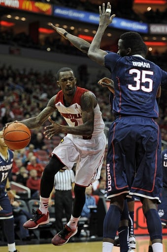 Mar 8, 2014; Louisville, KY, USA; Louisville Cardinals guard Russ Smith (2) looks to pass against Connecticut Huskies center Amida Brimah (35) during the second half at KFC Yum! Center. Louisville defeated Connecticut 81-48.  Mandatory Credit: Jamie Rhodes-USA TODAY Sports