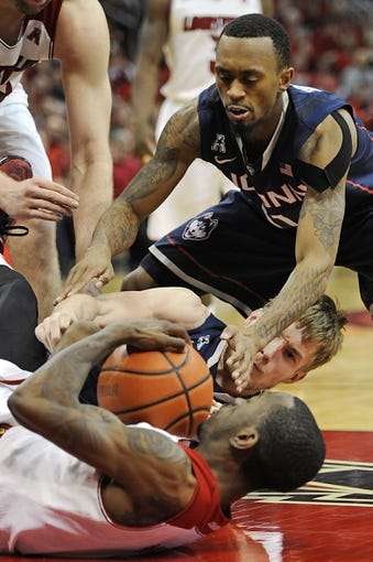 Mar 8, 2014; Louisville, KY, USA; Connecticut Huskies guard Ryan Boatright (11) and guard/forward Niels Giffey (5) battle for a loose ball with Louisville Cardinals guard Russ Smith (2) during the second half at KFC Yum! Center. Louisville defeated Connecticut 81-48.  Mandatory Credit: Jamie Rhodes-USA TODAY Sports