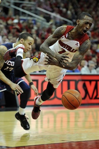 Mar 8, 2014; Louisville, KY, USA; Louisville Cardinals guard Russ Smith (2) looses the ball under the pressure of Connecticut Huskies guard Shabazz Napier (13) during the second half at KFC Yum! Center. Louisville defeated Connecticut 81-48.  Mandatory Credit: Jamie Rhodes-USA TODAY Sports