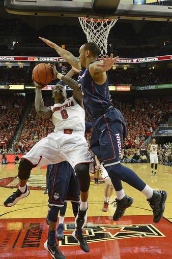 Mar 8, 2014; Louisville, KY, USA; Louisville Cardinals guard Terry Rozier (0) shoots against Connecticut Huskies guard Shabazz Napier (13) during the second half at KFC Yum! Center. Louisville defeated Connecticut 81-48.  Mandatory Credit: Jamie Rhodes-USA TODAY Sports