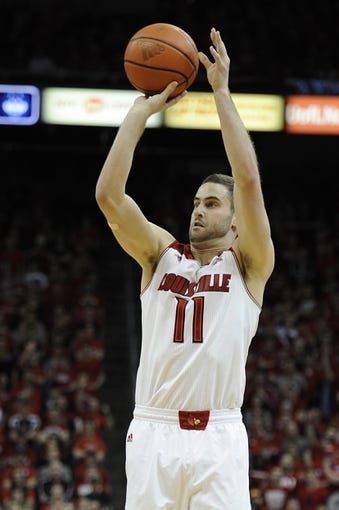 Mar 8, 2014; Louisville, KY, USA; Louisville Cardinals guard/forward Luke Hancock (11) shoots against the Connecticut Huskies during the second half at KFC Yum! Center. Louisville defeated Connecticut 81-48.  Mandatory Credit: Jamie Rhodes-USA TODAY Sports
