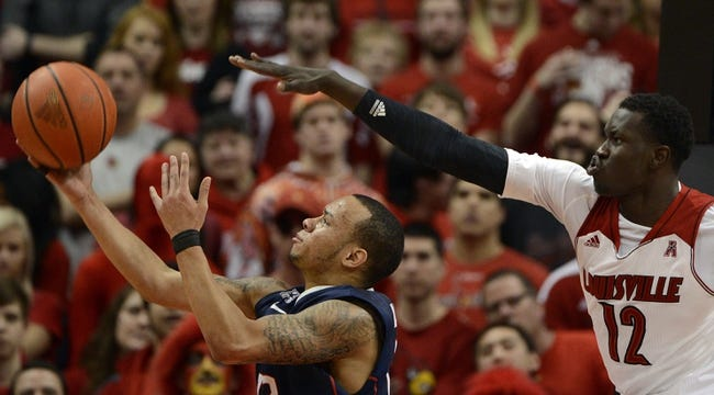 Mar 8, 2014; Louisville, KY, USA; Connecticut Huskies guard Shabazz Napier (13) shoots against Louisville Cardinals forward/center Mangok Mathiang (12) during the second half at KFC Yum! Center. Louisville defeated Connecticut 81-48.  Mandatory Credit: Jamie Rhodes-USA TODAY Sports