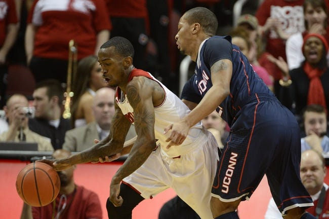 Mar 8, 2014; Louisville, KY, USA; Louisville Cardinals guard Russ Smith (2) dribbles against Connecticut Huskies guard Omar Calhoun (21) during the second half at KFC Yum! Center. Louisville defeated Connecticut 81-48.  Mandatory Credit: Jamie Rhodes-USA TODAY Sports