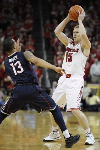 Mar 8, 2014; Louisville, KY, USA; Louisville Cardinals guard Tim Henderson (15) looks to pass against Connecticut Huskies guard Shabazz Napier (13) during the second half at KFC Yum! Center. Louisville defeated Connecticut 81-48.  Mandatory Credit: Jamie Rhodes-USA TODAY Sports