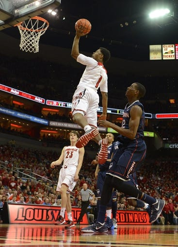 Mar 8, 2014; Louisville, KY, USA; Louisville Cardinals guard Anton Gill (1) shoots against Connecticut Huskies forward Kentan Facey (12) during the second half at KFC Yum! Center. Louisville defeated Connecticut 81-48.  Mandatory Credit: Jamie Rhodes-USA TODAY Sports