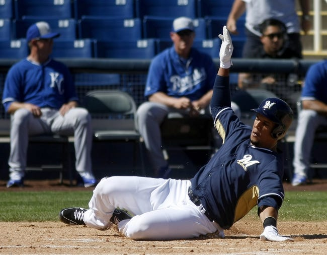 Mar 8, 2014; Phoenix, AZ, USA; Milwaukee Brewers center fielder Carlos Gomez (27) slides home safely in the first inning against the Kansas City Royals at Maryvale Baseball Park. Mandatory Credit: Rick Scuteri-USA TODAY Sports