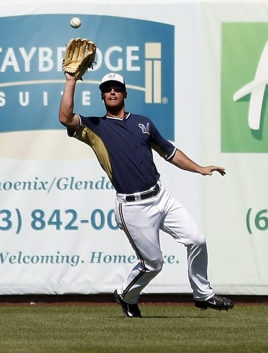 Mar 8, 2014; Phoenix, AZ, USA; Milwaukee Brewers center fielder Carlos Gomez (27) makes the running catch against the Kansas City Royals in the fourth inning at Maryvale Baseball Park. Mandatory Credit: Rick Scuteri-USA TODAY Sports