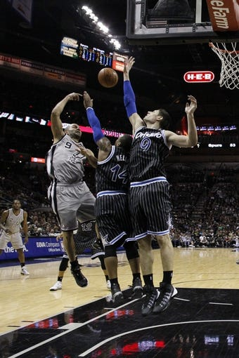Mar 8, 2014; San Antonio, TX, USA; San Antonio Spurs guard Tony Parker (9) passes the ball under the basket over Orlando Magic guard Jameer Nelson (14) and center Nikola Vucevic (9) during the first half at AT&T Center. Mandatory Credit: Soobum Im-USA TODAY Sports