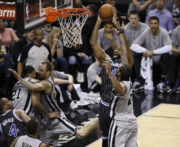 Mar 8, 2014; San Antonio, TX, USA; Orlando Magic forward Kyle O'Quinn (2) shoots the ball as San Antonio Spurs forward Kawhi Leonard (2) defends during the second half at AT&T Center. The Spurs won 121-112. Mandatory Credit: Soobum Im-USA TODAY Sports