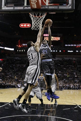 Mar 8, 2014; San Antonio, TX, USA; Orlando Magic forward Maurice Harkless (21) goes for a dunk as he is defended by San Antonio Spurs forward Tim Duncan (21) during the second half at AT&T Center. The Spurs won 121-112. Mandatory Credit: Soobum Im-USA TODAY Sports