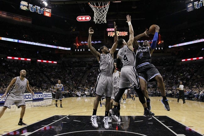 Mar 8, 2014; San Antonio, TX, USA; Orlando Magic guard Arron Afflalo (4) shoots the ball as San Antonio Spurs guard Danny Green (4) and forward Kawhi Leonard (2) defend during the second half at AT&T Center. The Spurs won 121-112. Mandatory Credit: Soobum Im-USA TODAY Sports