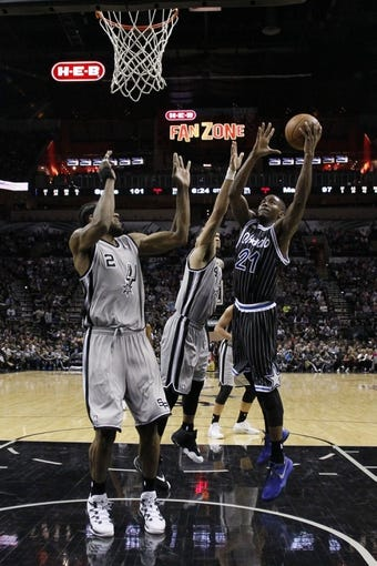 Mar 8, 2014; San Antonio, TX, USA; Orlando Magic forward Maurice Harkless (21) shoots the ball as San Antonio Spurs guard Danny Green (4) and forward Kawhi Leonard (2) defend during the second half at AT&T Center. The Spurs won 121-112. Mandatory Credit: Soobum Im-USA TODAY Sports