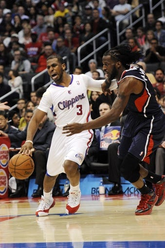 Mar 8, 2014; Los Angeles, CA, USA; Los Angeles Clippers guard Chris Paul (3) moves the ball defended by Atlanta Hawks forward DeMarre Carroll (5) during the third quarter at Staples Center. The Los Angeles Clippers defeated the Atlanta Hawks 109-108. Mandatory Credit: Kelvin Kuo-USA TODAY Sports