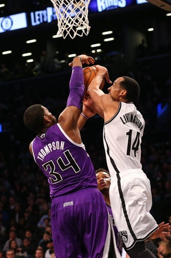Mar 9, 2014; Brooklyn, NY, USA;  Sacramento Kings power forward Jason Thompson (34) fouls Brooklyn Nets point guard Shaun Livingston (14) at the basket during the third quarter at Barclays Center. Brooklyn Nets won 104-89.  Mandatory Credit: Anthony Gruppuso-USA TODAY Sports