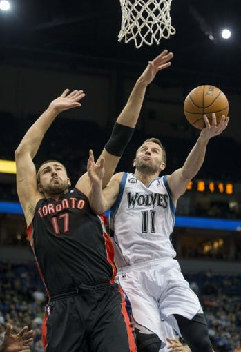 Mar 9, 2014; Minneapolis, MN, USA; Minnesota Timberwolves point guard J.J. Barea (11) goes up for a layup past Toronto Raptors center Jonas Valanciunas (17) in the second half at Target Center. The Raptors won 111-104. Mandatory Credit: Jesse Johnson-USA TODAY Sports