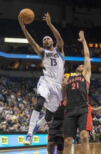 Mar 9, 2014; Minneapolis, MN, USA; Minnesota Timberwolves small forward Corey Brewer (13) goes up for a layup past Toronto Raptors point guard Greivis Vasquez (21) in the second half at Target Center. The Raptors won 111-104. Mandatory Credit: Jesse Johnson-USA TODAY Sports
