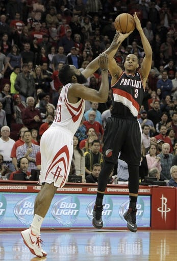 Mar 9, 2014; Houston, TX, USA; Portland Trail Blazers shooting guard C.J. McCollum (3) shoots the ball over Houston Rockets shooting guard James Harden (13) during the overtime period at Toyota Center. Mandatory Credit: Andrew Richardson-USA TODAY Sports