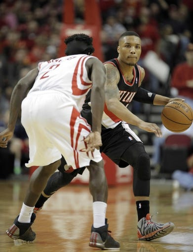 Mar 9, 2014; Houston, TX, USA; Portland Trail Blazers point guard Damian Lillard (0) is defended by Houston Rockets point guard Patrick Beverley (2) during the fourth quarter at Toyota Center. Mandatory Credit: Andrew Richardson-USA TODAY Sports
