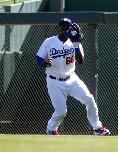 Mar 10, 2014; Phoenix, AZ, USA; Los Angeles Dodgers right fielder Yasiel Puig (66) makes the catch in the fourth inning against the Oakland Athletics at Camelback Ranch. Mandatory Credit: Rick Scuteri-USA TODAY Sports