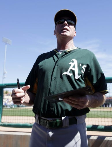 Mar 10, 2014; Phoenix, AZ, USA; Oakland Athletics manager Bob Melvin (6) autographs items for fans before a game against the Los Angeles Dodgers at Camelback Ranch. Mandatory Credit: Rick Scuteri-USA TODAY Sports