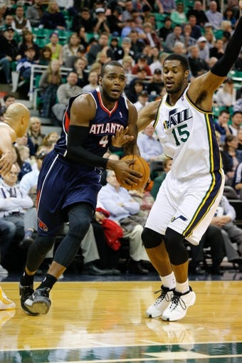 Mar 10, 2014; Salt Lake City, UT, USA; Atlanta Hawks power forward Paul Millsap (4) is fouled by Utah Jazz center Derrick Favors (15) while driving to the basket during the first quarter at EnergySolutions Arena. Mandatory Credit: Chris Nicoll-USA TODAY Sports