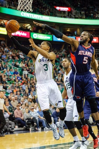 Mar 10, 2014; Salt Lake City, UT, USA; Utah Jazz point guard Trey Burke (3) lays the ball into the basket while Atlanta Hawks small forward DeMarre Carroll (5) tries to block the shot during the fourth quarter at EnergySolutions Arena. The Atlanta Hawks won the game 112-110. Mandatory Credit: Chris Nicoll-USA TODAY Sports