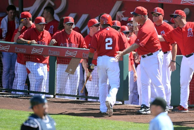 Mar 11, 2014; Tempe, AZ, USA; Los Angeles Angels shortstop Erick Aybar (2) is congratulated by coaches and teammates after  scoring  a run against the Seattle Mariners at Tempe Diablo Stadium. Mandatory Credit: Joe Camporeale-USA TODAY Sports