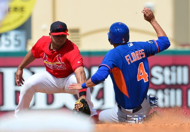 Mar 11, 2014; Jupiter, FL, USA; St. Louis Cardinals shortstop Jhonny Peralta (27) tags out New York Mets third baseman Wilmer Flores (4) on a stolen base attempt at Roger Dean Stadium. The Mets defeated the Cardinals 9-8. Mandatory Credit: Scott Rovak-USA TODAY Sports