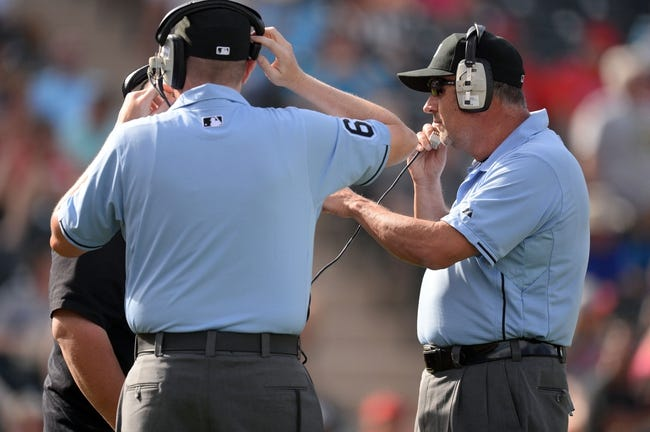 Mar 11, 2014; Tempe, AZ, USA; Umpires review a call in the eighth inning of the game between the Los Angeles Angels and the Seattle Mariners at Tempe Diablo Stadium. Mandatory Credit: Joe Camporeale-USA TODAY Sports