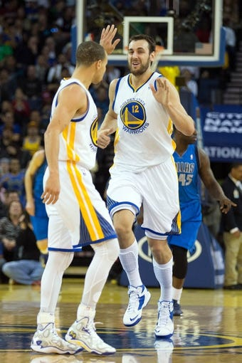 Mar 11, 2014; Oakland, CA, USA; Golden State Warriors center Andrew Bogut (12) high fives guard Stephen Curry (30) after a basket against the Dallas Mavericks during the second quarter at Oracle Arena. Mandatory Credit: Kelley L Cox-USA TODAY Sports