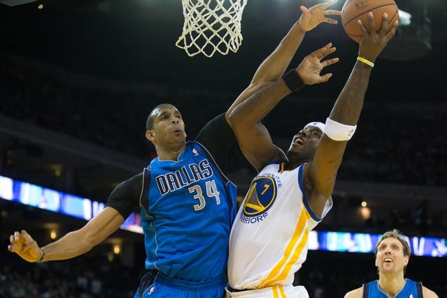 Mar 11, 2014; Oakland, CA, USA; Golden State Warriors center Jermaine O'Neal (7) shoots the ball against Dallas Mavericks forward Brandan Wright (34) during the fourth quarter at Oracle Arena. The Golden State Warriors defeated the Dallas Mavericks 108-85. Mandatory Credit: Kelley L Cox-USA TODAY Sports