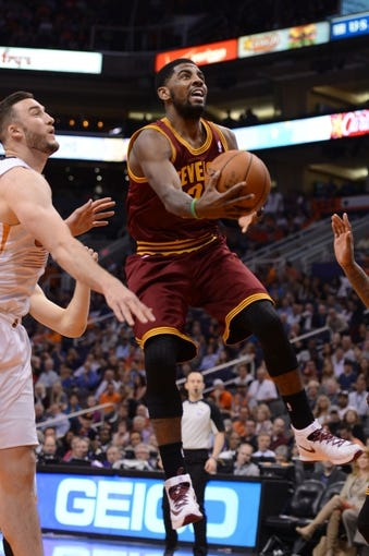 Mar 12, 2014; Phoenix, AZ, USA; Cleveland Cavaliers guard Kyrie Irving (2) shoots the ball in front of Phoenix Suns forward Miles Plumlee (22) in the first half at US Airways Center. Mandatory Credit: Jennifer Stewart-USA TODAY Sports