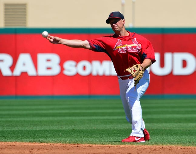 Mar 13, 2014; Jupiter, FL, USA; St. Louis Cardinals second baseman Mark Ellis (3) throws out a Atlanta Braves base runner at Roger Dean Stadium. The Cardinals defeated the Braves 11-0. Mandatory Credit: Scott Rovak-USA TODAY Sports