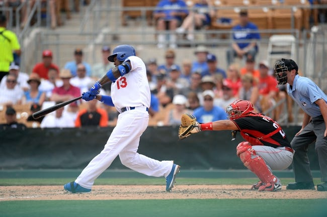 Mar 13, 2014; Phoenix, AZ, USA; Los Angeles Dodgers shortstop Hanley Ramirez (13) swings at a pitch against the Cincinnati Reds during a spring training game at Camelback Ranch. Mandatory Credit: Joe Camporeale-USA TODAY Sports