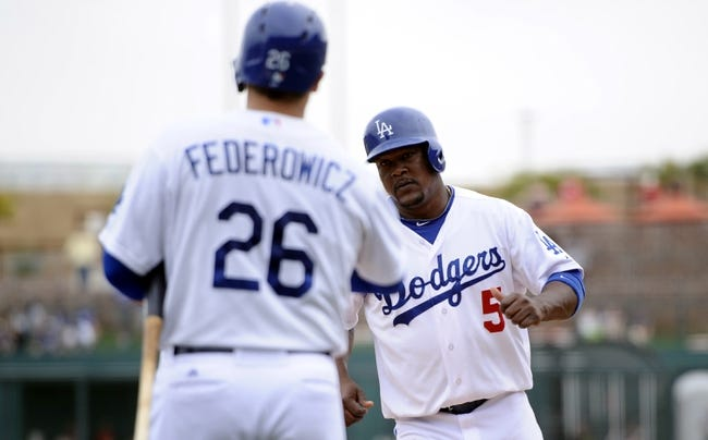 Mar 13, 2014; Phoenix, AZ, USA; Los Angeles Dodgers third baseman Juan Uribe (5) slaps hands with catcher Tim Federowicz (26) after scoring a run in the fourth inning of a spring training game against the Cincinnati Reds at Camelback Ranch. Mandatory Credit: Joe Camporeale-USA TODAY Sports